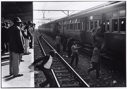 Ernest Cole, Which black train to take is matter of guesswork. They have no destination signs and no announcement of arrivals is made. Head car may be numbered to show its route, but number is often wrong. In confusion, passengers sometimes jump across track, and some are killed by express trains. Caption from House of Bondage, date unknown, published 1967. Silver gelatin print, 8 5/8 x 12 5/8 in. © The Ernest Cole Family Trust. Image courtesy the Hasselblad Foundation.