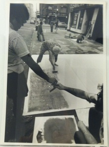 Peter Moore, photograph of Sari Dienes demonstrating the street rubbing process, 1970. Gelatin silver print, 6.5 x 9.75 in.